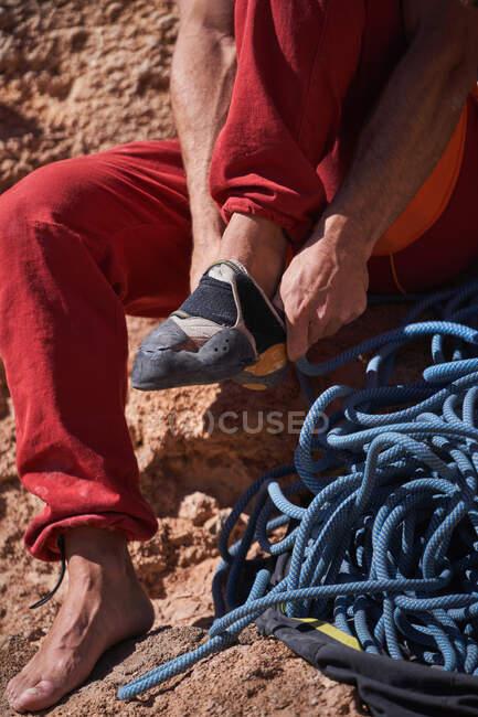 Alpinista masculino irreconhecível em sportswear vermelho sentado em solo rochoso perto de corda azul e usando sapatos de escalada antes de subir — Fotografia de Stock