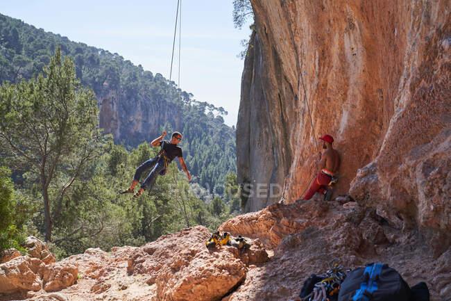 Зверху самець альпініст з сонцезахисними окулярами висить на мотузці, а під час сходження з партнеркою, що не має сорочки, стоїть поруч у захисному спорядженні і тримає мотузку. — стокове фото