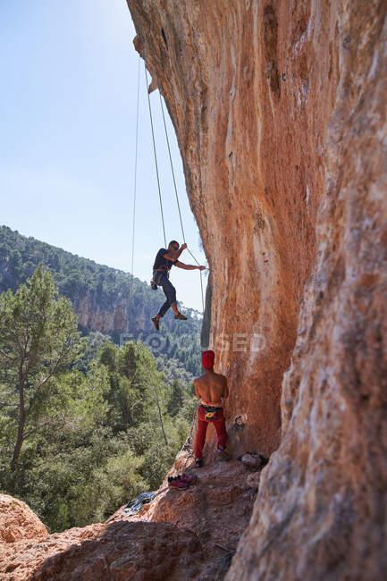 De cima vista do alpinista masculino com óculos de sol pendurados na corda enquanto ascende com o parceiro sem camisa de pé perto em engrenagem de segurança e segurando corda — Fotografia de Stock