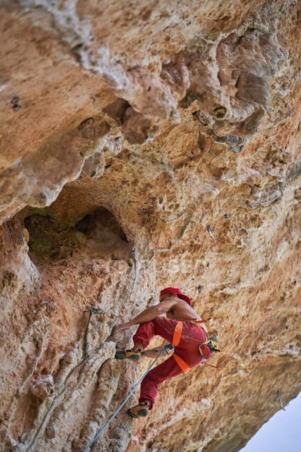 Знизу, у червоній шапці, альпініст, що піднімається на скелястий схил гори, у сонячний безхмарний день. — стокове фото