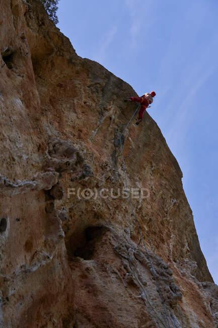 Dal basso di forte alpinista barbuto senza maglietta in berretto rosso arrampicata salita pendio roccioso di montagna in giornata soleggiata senza nuvole — Foto stock