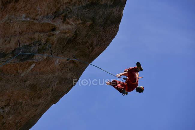 Dal basso vista dell'alpinista maschio con attrezzatura di sicurezza appesa alla corda mentre pratica l'arrampicata sul pendio roccioso della montagna in una giornata senza nuvole — Foto stock