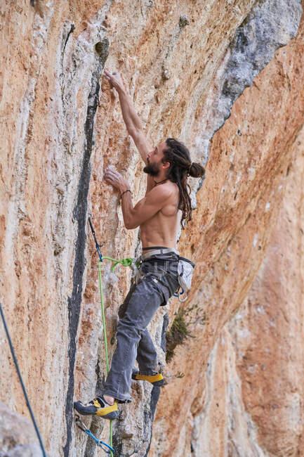 Знизу: безсоромний бородатий альпініст у безпечному обладнанні, який піднімається на скелястий схил гори і дивиться вгору. — стокове фото