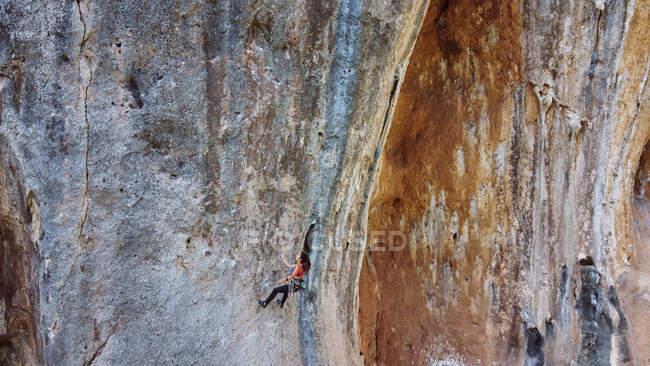 Сверху активная альпинистка в спортивной одежде с веревкой и защитным снаряжением, поднимающаяся по скалистому склону высокой горы в солнечный день — стоковое фото