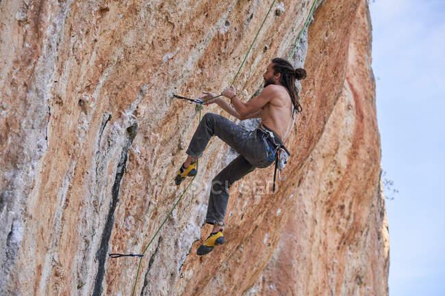 De baixo vista lateral de alpinista barbudo sem camisa em equipamentos de segurança subindo na encosta rochosa da montanha e olhando para cima — Fotografia de Stock