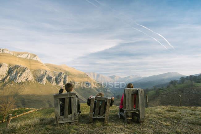 Дети в повседневной одежде сидят на деревянных скамейках на удаленном зеленом холме и наслаждаются видом во время посещения Испании — стоковое фото