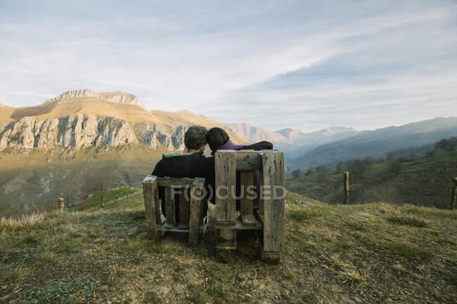 Pareja sentada en bancos de madera en la remota colina verde y disfrutando de la vista mientras visita España - foto de stock