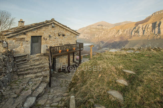 Old stone house with tiled roof and with wooden terrace located in rocky terrain in Cantabria — Stock Photo
