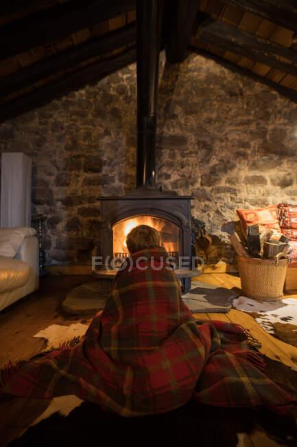 Kuscheliges Kind in kuschelige Schottenkarierte gehüllt sitzt auf Holzboden neben brennendem Kamin und schaut auf Feuer in Steinhaus in Kantabrien — Stockfoto