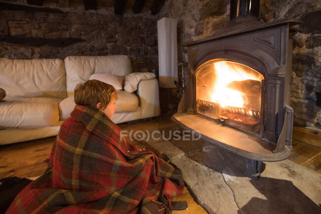 Cuddling kid wrapped in cozy tartan plaid sitting on wooden floor near burning fireplace and looking at fire in stone house in Cantabria — Stock Photo