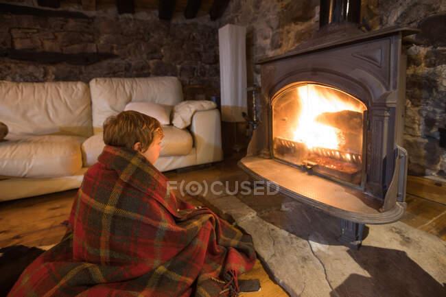 Puto carinhoso envolto em xadrez de tartan aconchegante sentado no chão de madeira perto de lareira em chamas e olhando para o fogo na casa de pedra na Cantábria — Fotografia de Stock