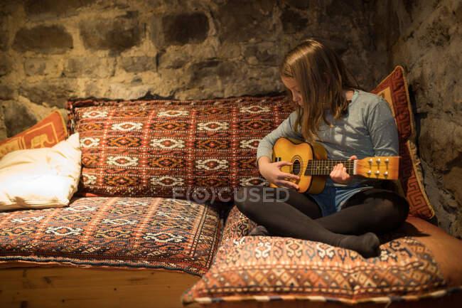 Зосереджена дівчина в повсякденному одязі, сидячи зі схрещеними ногами на зручному дивані і граючи на укулеле в кам