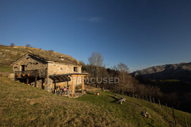 Shabby aged stone house with wooden terrace on slope of picturesque mountainous terrain in Cantabria — Stock Photo