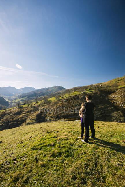Vista posterior de una excursionista anónima abrazando a los niños mientras está de pie en el prado verde y observa el pintoresco paisaje de las montañas en un día soleado en Cantabria - foto de stock