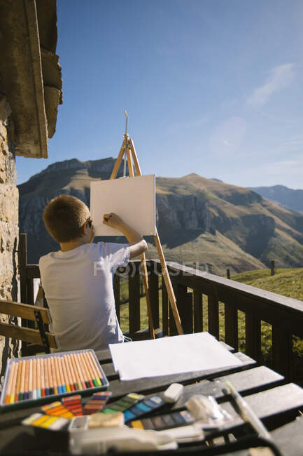 Back view of faceless boy in white t shirt sitting at easel on picturesque veranda of country house and drawing picture in Cantabria — Stock Photo