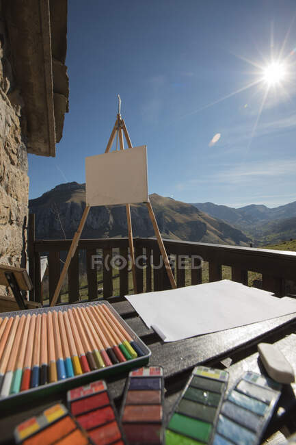 Set of colorful pencils and various painting tools placed on wooden table near easel with canvas on sunny terrace of old stone house in Spain — Stock Photo