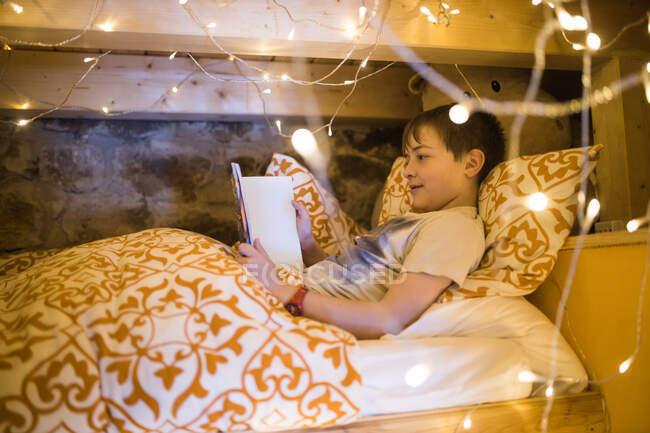 Зміст хлопчика лежить у затишному ліжку і використовує планшет, відпочиваючи в спальні прикрашеній блискучим затишним садом. — стокове фото