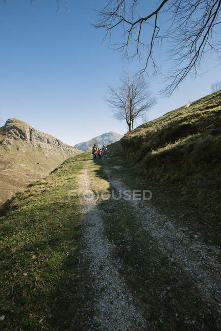 Hikers walking up rural roadway at slope of green hill in rocky mountains during trip to Spain — Stock Photo
