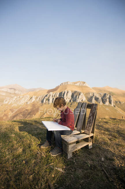 Side view of adorable child sitting on wooden bench and painting on canvas during weekend on background of magnificent mountainous landscape — Stock Photo