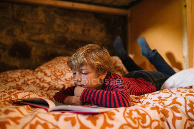 Dreamy child in casual wear lying on cozy bed and enjoying interesting fairy tale in story book for children — Stock Photo