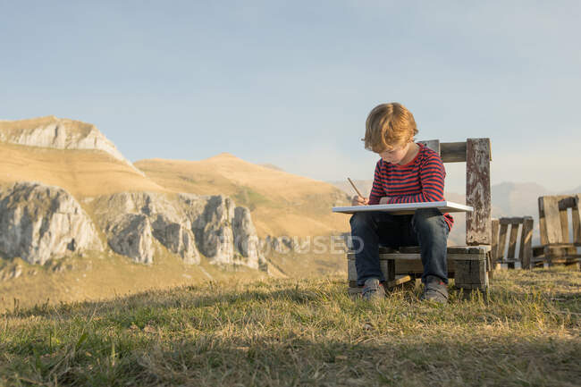 Adorable child sitting on wooden bench and painting on canvas during weekend on background of magnificent mountainous landscape — Stock Photo