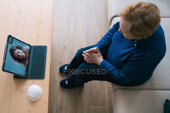 Старенька жінка спілкується з дочкою під час відеобесіди на ноутбуку. — стокове фото