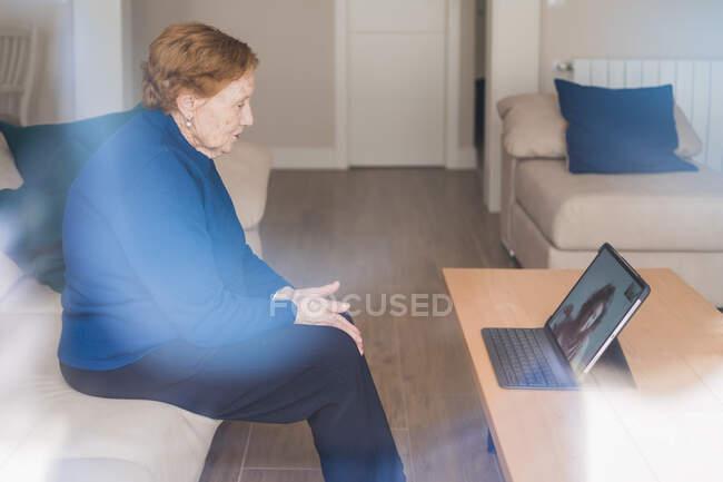 Vieja mujer comunicarse con su hija en el chat de vídeo en el ordenador portátil - foto de stock