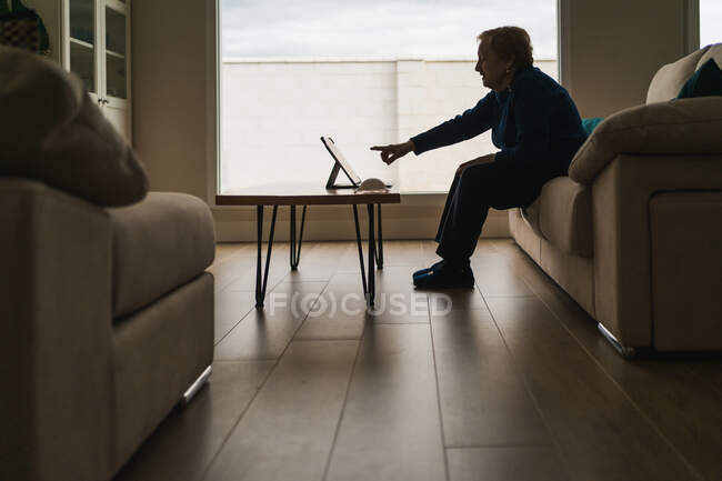Mujer mayor comunicarse con un amigo durante el chat de vídeo en el ordenador portátil - foto de stock