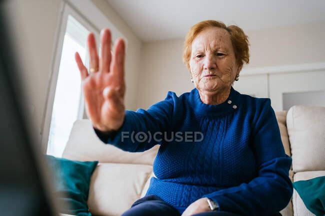 Bajo ángulo de sonriente anciano gesto femenino y amigo saludo mientras que tener conversación de vídeo en el ordenador portátil durante el autoaislamiento para la prevención de coronavirus en el hogar - foto de stock