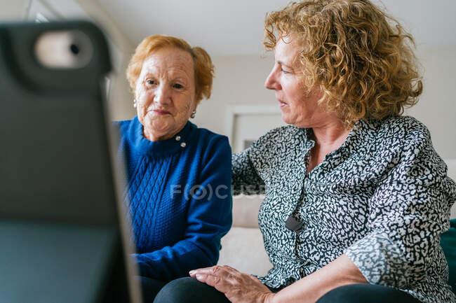 Mujeres teniendo conversación de vídeo en el ordenador portátil en casa - foto de stock