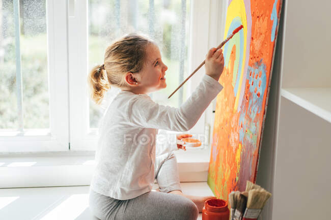 Creative blond girl in casual clothes sitting on window sill against window and painting with paintbrush large multi colored rainbow on orange canvas — Stock Photo