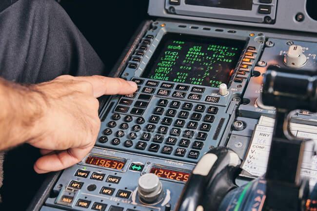 Crop pilota maschio anonimo utilizzando la tastiera del sistema di gestione del volo in cabina di pilotaggio di aeromobili moderni durante il volo — Foto stock