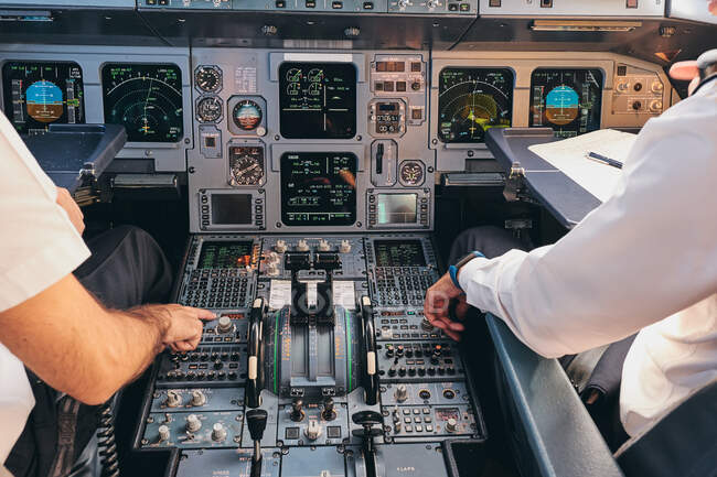 Vista posteriore di coltura anonimo capitano maschio e pilota seduto in cabina di pilotaggio di aeroplano moderno e attrezzature di controllo durante la preparazione per la partenza — Foto stock