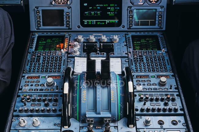 Dall'alto delle leve di controllo della potenza del motore e degli interruttori sul cruscotto all'interno dell'aereo passeggeri civile contemporaneo — Foto stock