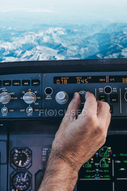 Back view of crop anonymous male pilot turning switch on control panel in cockpit during flight over rocky terrain — Stock Photo
