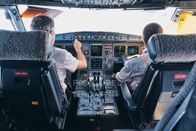 Back view of male pilot and co pilot using instrument panel in cockpit of modern passenger aircraft during flight — Stock Photo
