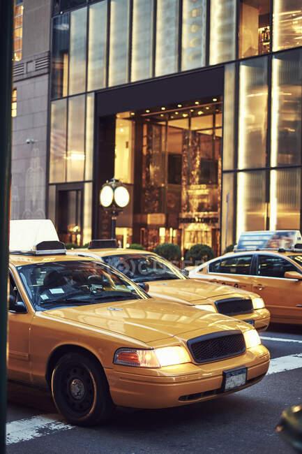 Современные желтые такси ездят по мощеной улице в центральном районе Нью-Йорка — стоковое фото