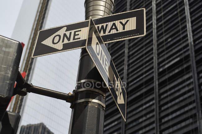 Desde abajo de una vía señales de tráfico en la encrucijada con edificios altos modernos en el fondo en la ciudad de Nueva York - foto de stock