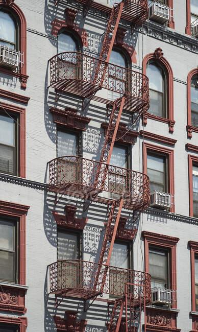 Знизу на фасаді класичного багатоквартирного будинку з металевими сходами від пожежі на вулиці Нью - Йорка. — стокове фото