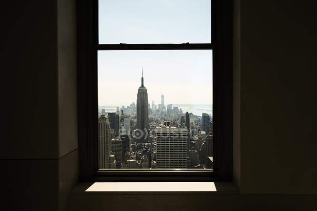 New York city view with skyscrapers and Empire State Building seen from narrow window in sunlight — Stock Photo