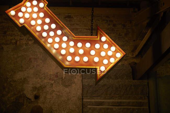 Angle bas de flèche rouge éclairée avec des ampoules lumineuses suspendues sur un mur minable sur la rue de la ville de nuit — Photo de stock