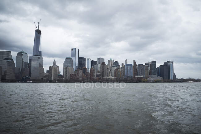 Contemporary skyscrapers of New York City seen from river against blue cloudy sky in sunny day — Stock Photo