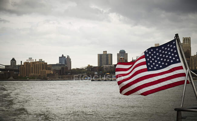 National flag of USA waving on pole of floating vessel against cloudy sky near New York City coast — Stock Photo