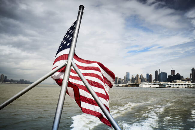 Государственный флаг США машет на полюсе плавучего судна против облачного неба вблизи побережья Нью-Йорка — стоковое фото
