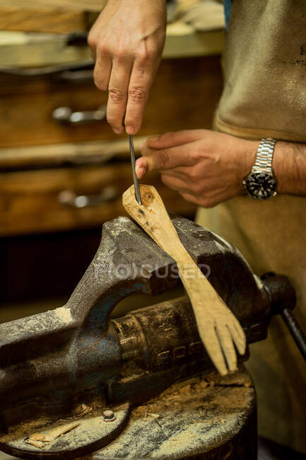 Crop anonymous carpenter in apron using chisel for making hole in wooden product clamped in workbench while working in workshop — Stock Photo