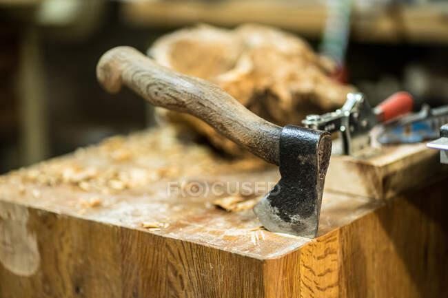 Шаббі сокира з дерев'яною ручкою, що стирчить з великого квадратного дерев'яного столу з тирсою на задньому плані столярних інструментів і шматок дерев'яного сировини в майстерні. — стокове фото