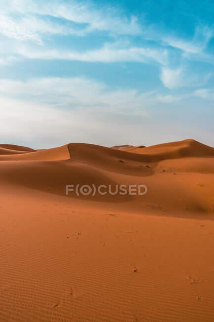 Paesaggio desertico minimalista con dune sabbiose sotto il cielo nuvoloso blu — Foto stock