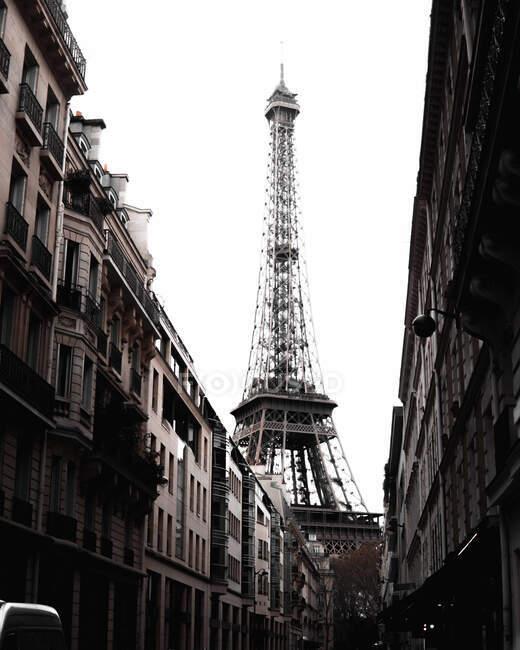 Esterno monocromatico di alta splendida Torre Eiffel alla fine della stretta strada con vecchi splendidi edifici monumentali sullo sfondo di cielo bianco brillante a Parigi — Foto stock