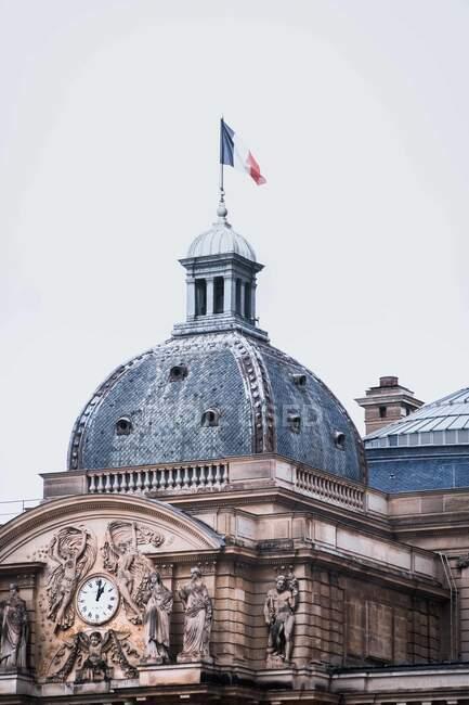 Famosi edifici storici tetto di architettura mozzafiato monumento Palazzo di Lussemburgo con magnifica statua dell'orologio della città sul muro e sventola bandiera francese in cima alla torre nel giardino lussemburghese durante il giorno — Foto stock