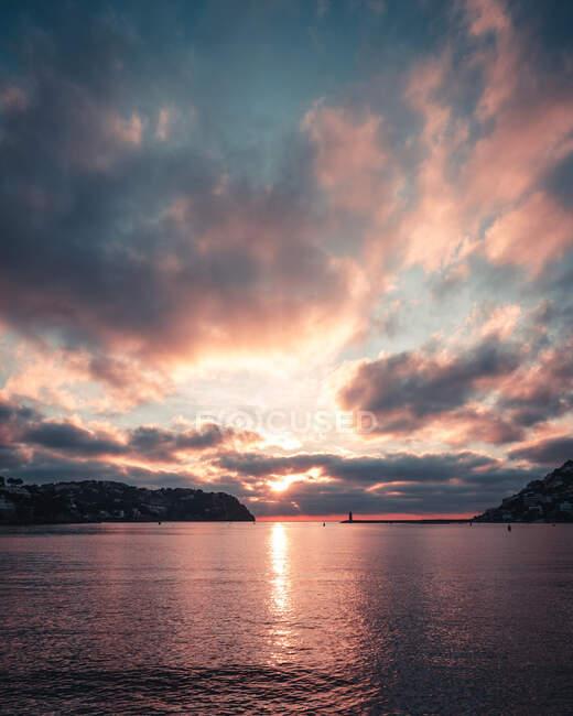 Nuvole galleggianti sul cielo al tramonto sopra l'acqua di mare increspata e la costa dell'isola di Maiorca in serata in Spagna — Foto stock